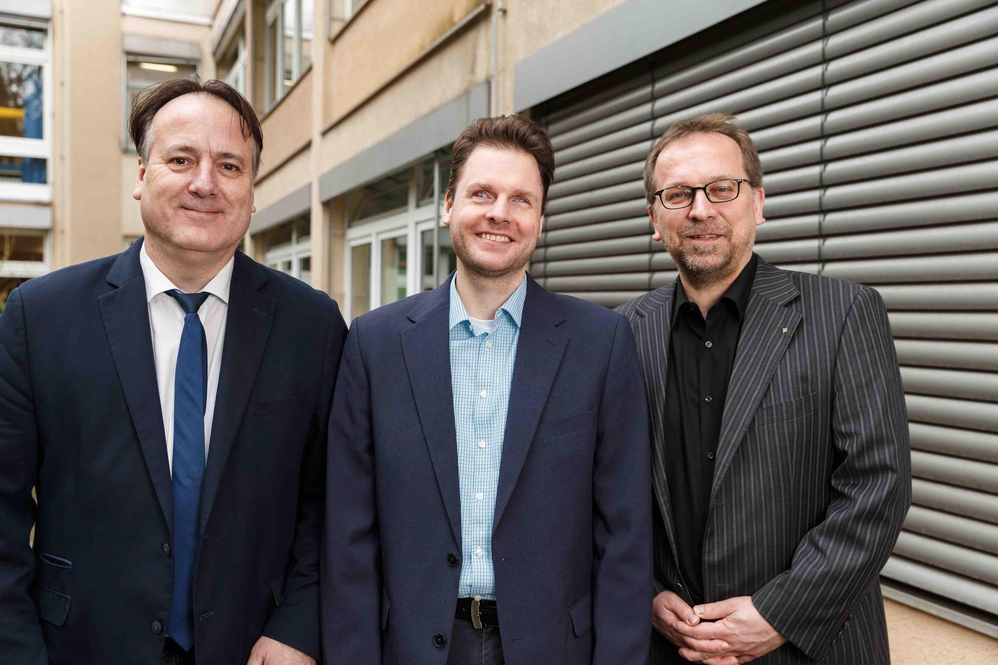 Drei Männer in Anzügen lächeln in die Kamera. Von links nach rechts: Michael Schupke, Stephan Heinke und Sven Hänszke.