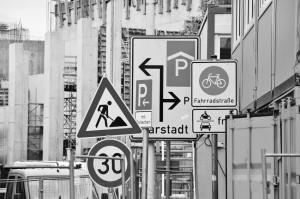 In schwarz weiß sind Straßenschilder und Bauschilder unübersichtlich vor einer Baustelle.