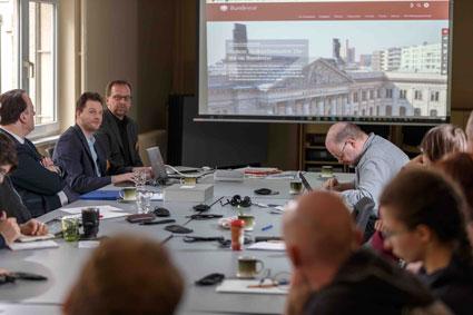In einem Seminarraum sitzt eine Gruppe Menschen an einem Tisch. Auf der Leinwand ist die Seite des Bundestages geöffnet. Diese wird gerade auf ihre Barrierefreiheit hin überprüft.