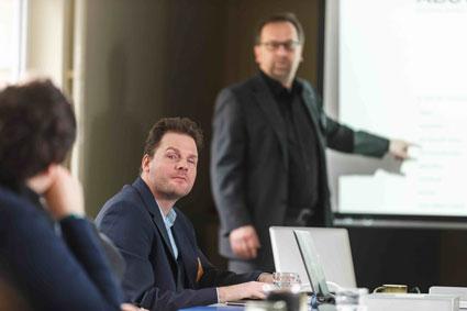 In der Bildmitte ist Stephan Heinke, der konzentriert nach links schaut. Im Hintergrund steht Sven Hänszke und zeigt auf eine Beamerleinwand.